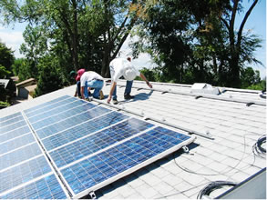 Crews installing solar thermal collectors on the roof of a zero-energy house